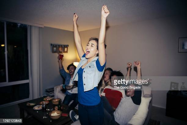 friends cheering while watching sports on tv at home - celebration stock pictures, royalty-free photos & images