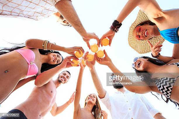 Friends cheering with beer on beach