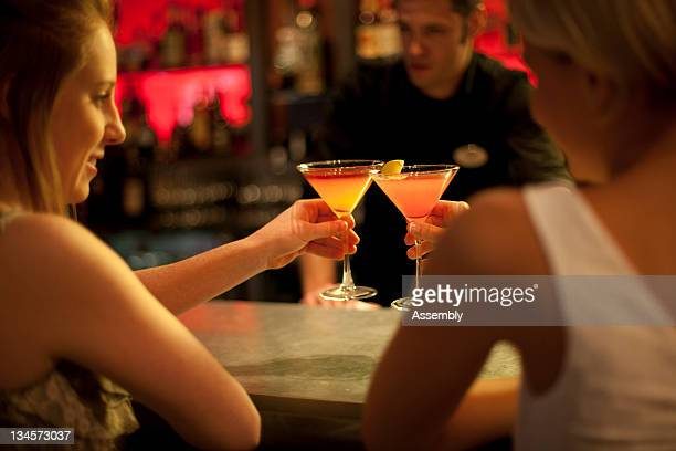 Friends cheers martinis at a bar.