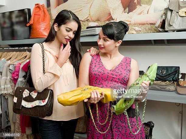 friends choosing between two colorful clutch bags