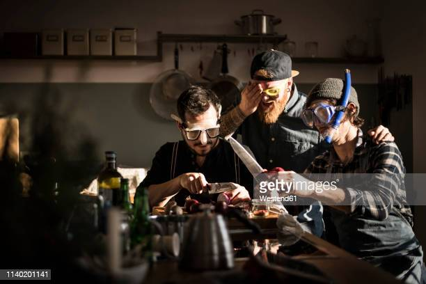 friends chopping onions with swimming goggles - humor stock-fotos und bilder