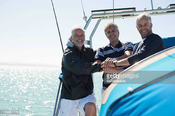 Friends clasping hands on deck of boat