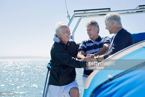 amis clasping mains sur le pont du bateau - bateau de plaisance photos et images de collection