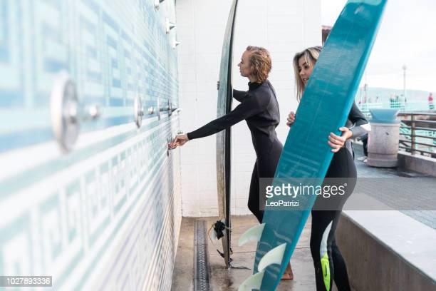 amis, nettoyage des planches de surf à la fin d'une longue journée sur la plage en californie - jeune femme sous la douche photos et images de collection