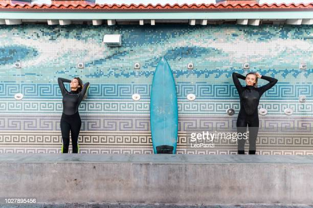 Friends cleaning surf boards at the end of a long day on the beach in California