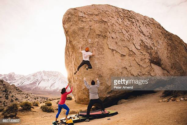 Friends climbing boulder, Buttermilk Boulders, Bishop, California, USA