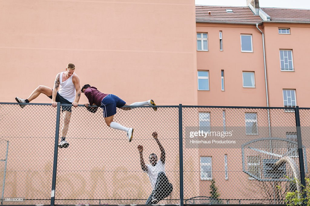 Friends Climbing Over Fence : Stock Photo