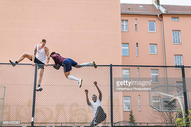 friends climbing over fence - ungestellt stock-fotos und bilder
