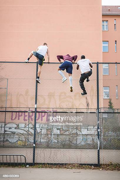 friends climbing over fence - klettern stock-fotos und bilder