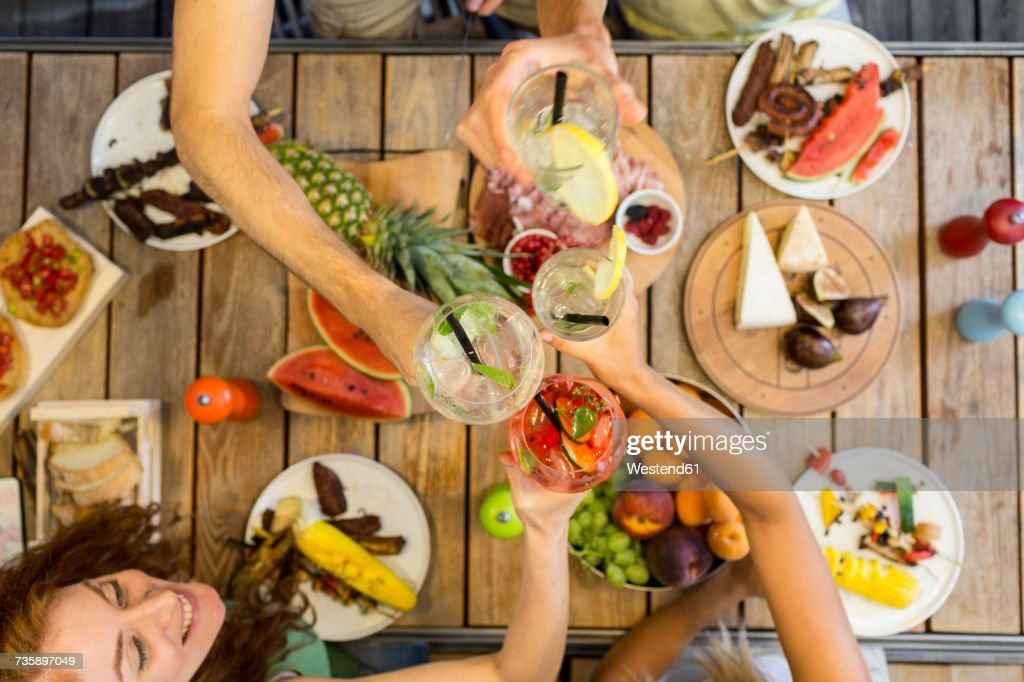 Friends clinking glasses above outdoor table : Stock Photo