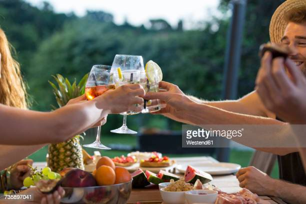 Friends clinking glasses at outdoor table