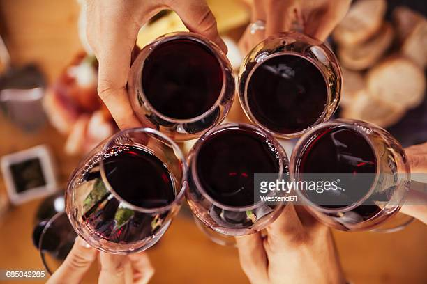 friends clinking red wine glasses - wine glass stock photos and pictures