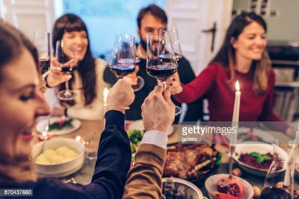 Freunde, die klirrende Gläser Wein am Weihnachtstisch