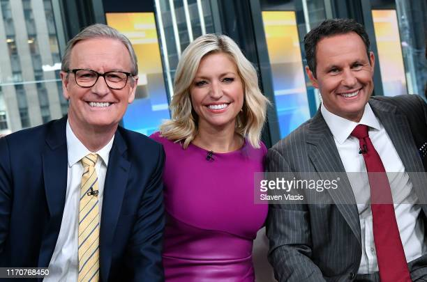 FOX Friends cohosts Steve Doocy Ainsley Earhardt and Brian Kilmeade pose for photos during FOX Friends at Fox News Channel Studios on September 24...