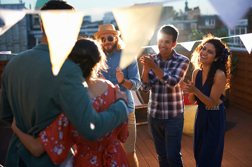 Friends congratulating couple at early evening engagement party - gettyimageskorea