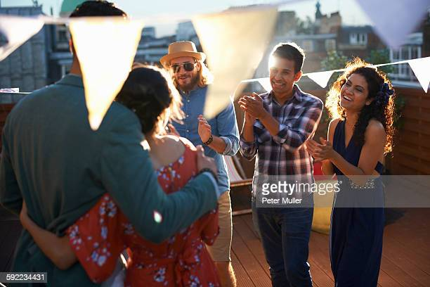 Friends congratulating couple at early evening engagement party