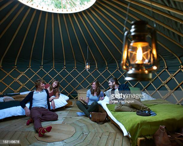 Friends congregated around beds inside yurt.