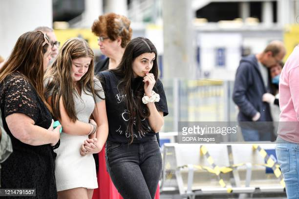 Friends console each other in front of the floral memorial at Victoria station during the commemoration People gather at Victoria station to mark the...