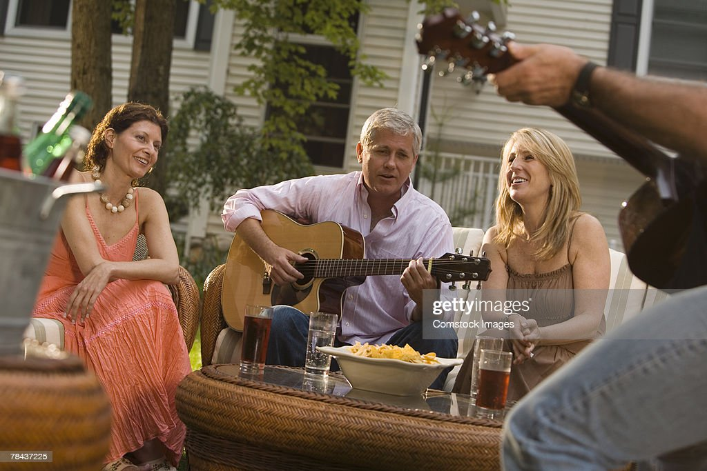 Friends conversing and playing guitar at a party : Stock Photo