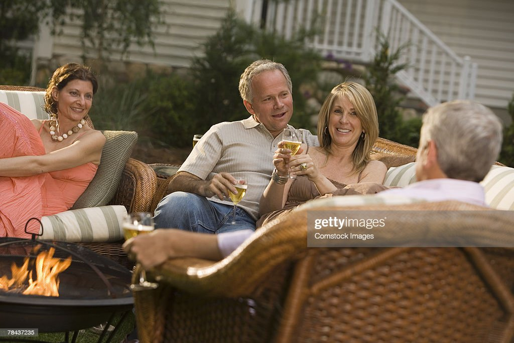 Friends conversing at a party : Stockfoto
