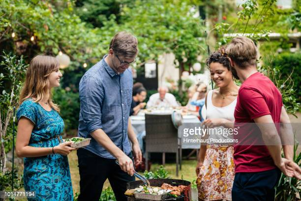 friends cooking together at bbq with family - barbecue grill stock pictures, royalty-free photos & images