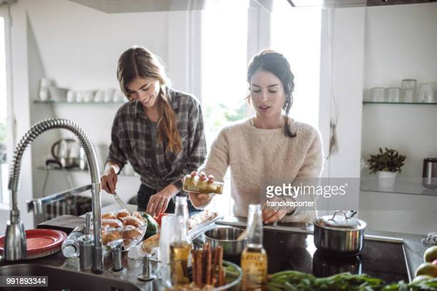 friends cooking together at home - kitchen stock pictures, royalty-free photos & images