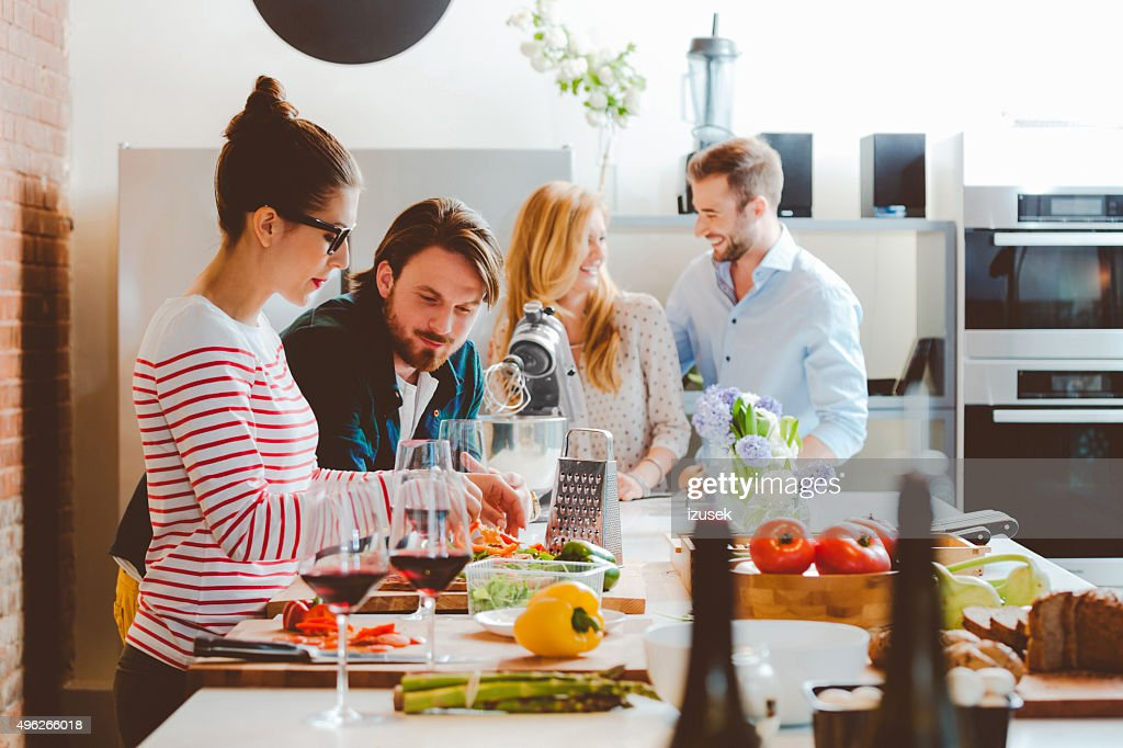 Friends cooking together in the modern kitchen : Stock Photo