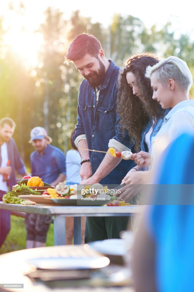 Friends cooking together : Stock Photo