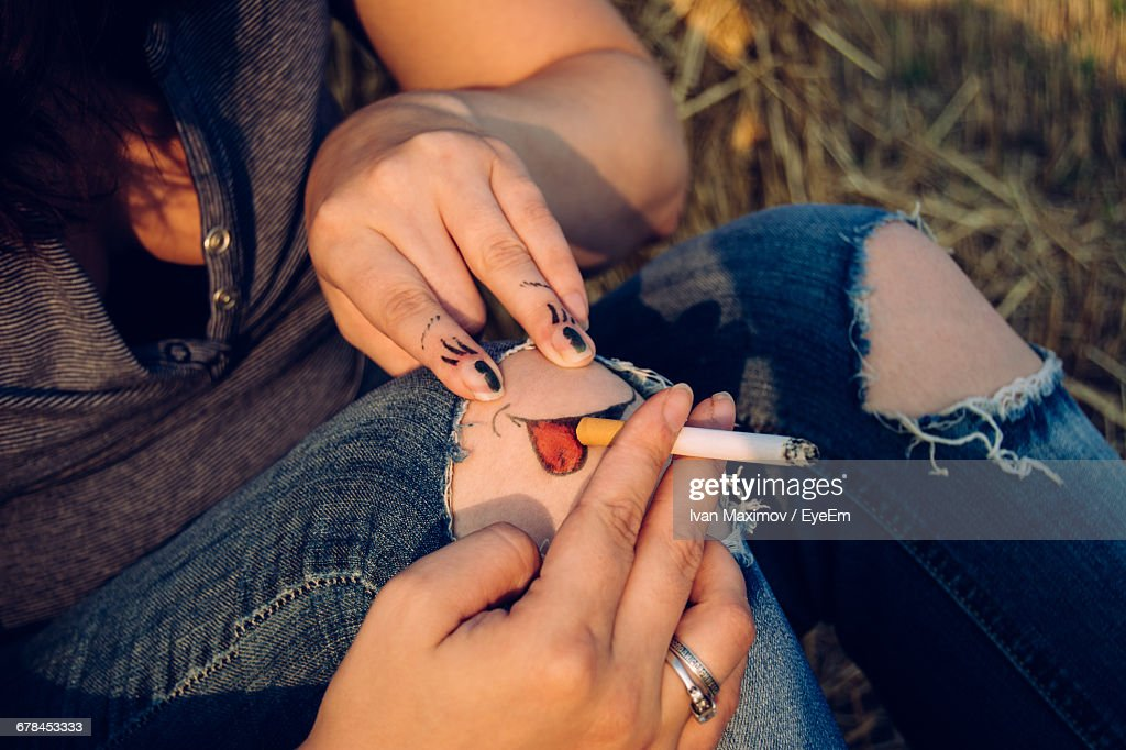 Friends Creating Illusion Of Knee Smoking Cigarette
