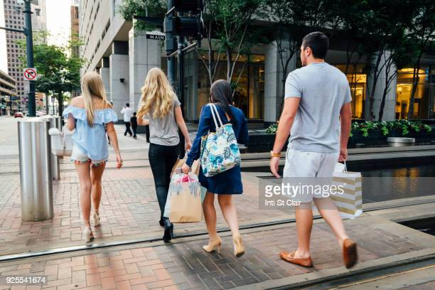 Friends crossing street in city carrying shopping bags