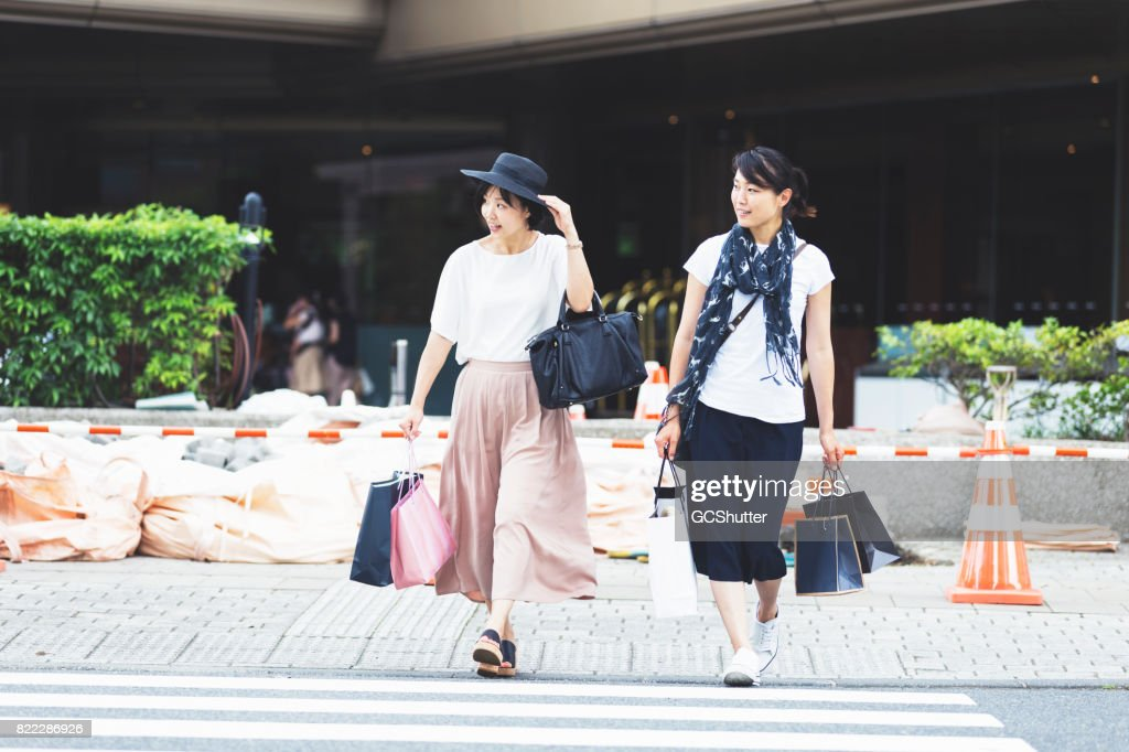 Friends crossing the street with several bags in hand : Stock Photo