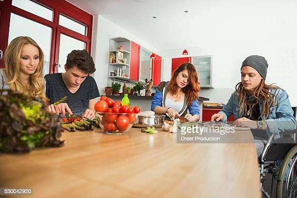 Friends cutting vegetables in the kitchen, Munich, Bavaria, Germany