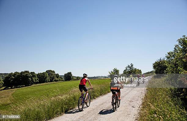 friends cycling on road against clear sky - thuringia stock pictures, royalty-free photos & images