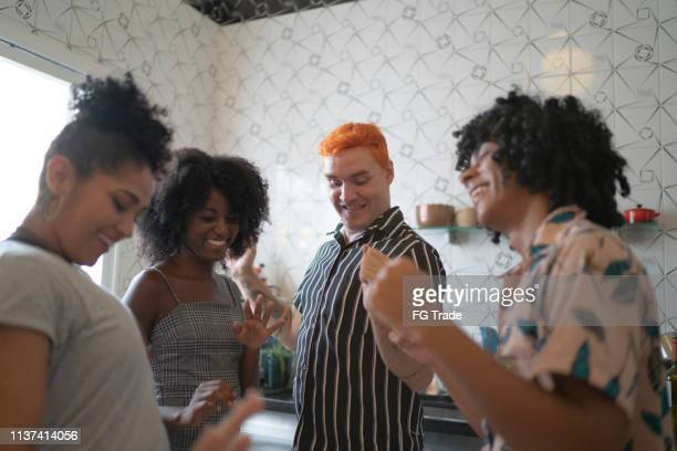 Friends dancing and having fun at kitchen
