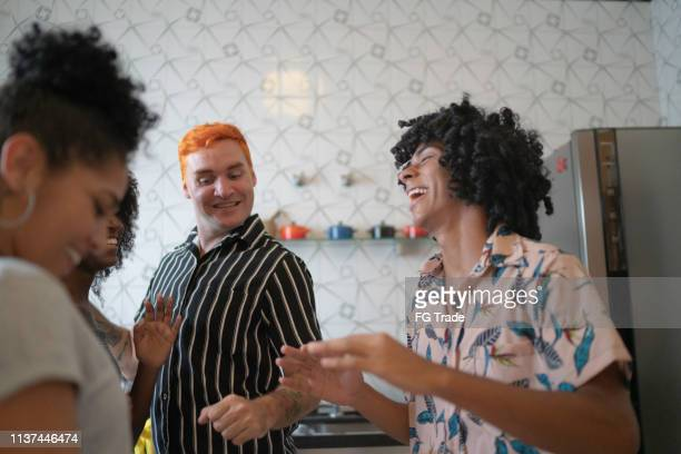 friends dancing and having fun at kitchen - polyamory stock photos and pictures
