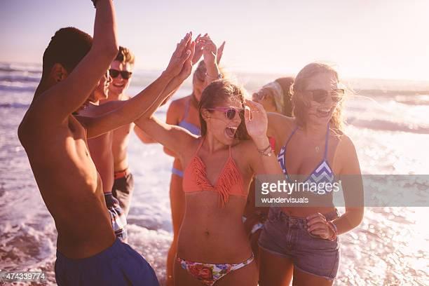 Amigos bailando y el fiving en la playa