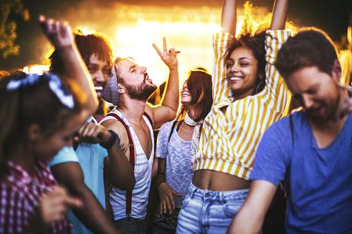 Friends dancing at a concert. 1003783908