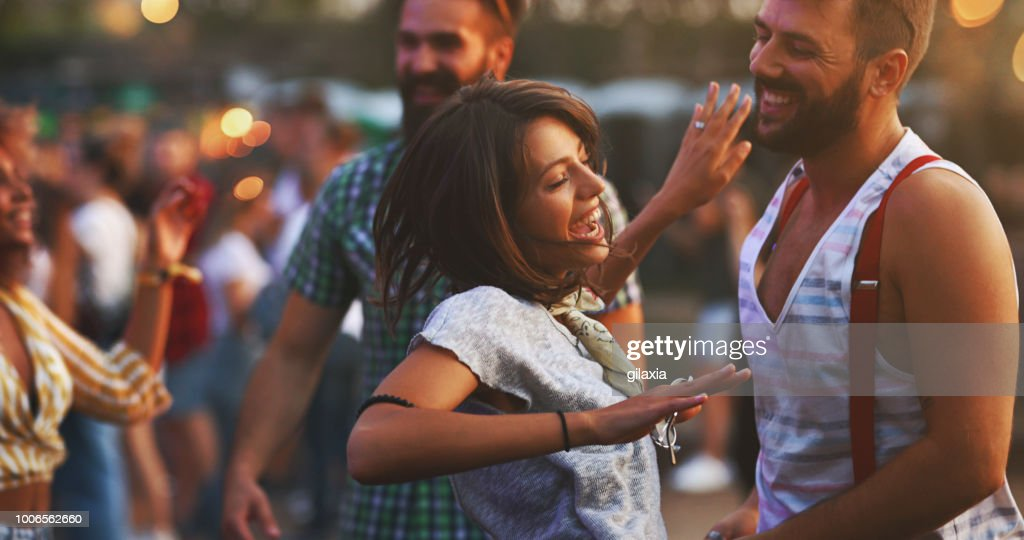 Friends dancing at a concert. : Stock Photo