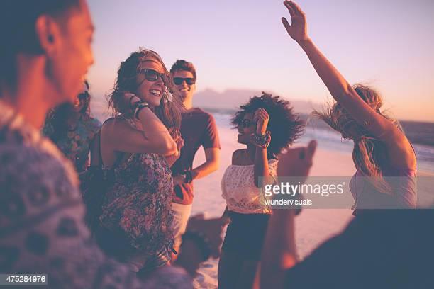 Friends dancing at a summer sunset beachparty