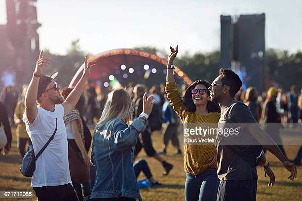 friends dancing at festival with arms in air - concert photos et images de collection