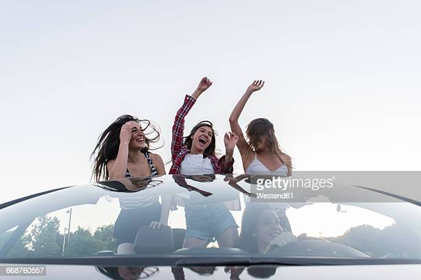 Friends dancing in convertible