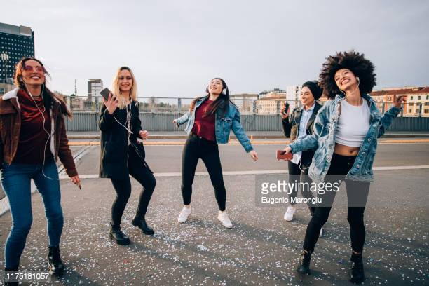 friends dancing in street to smartphone music, milan, italy - human settlement stock pictures, royalty-free photos & images
