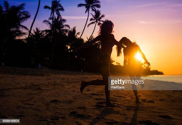friends dancing on a sunset beach