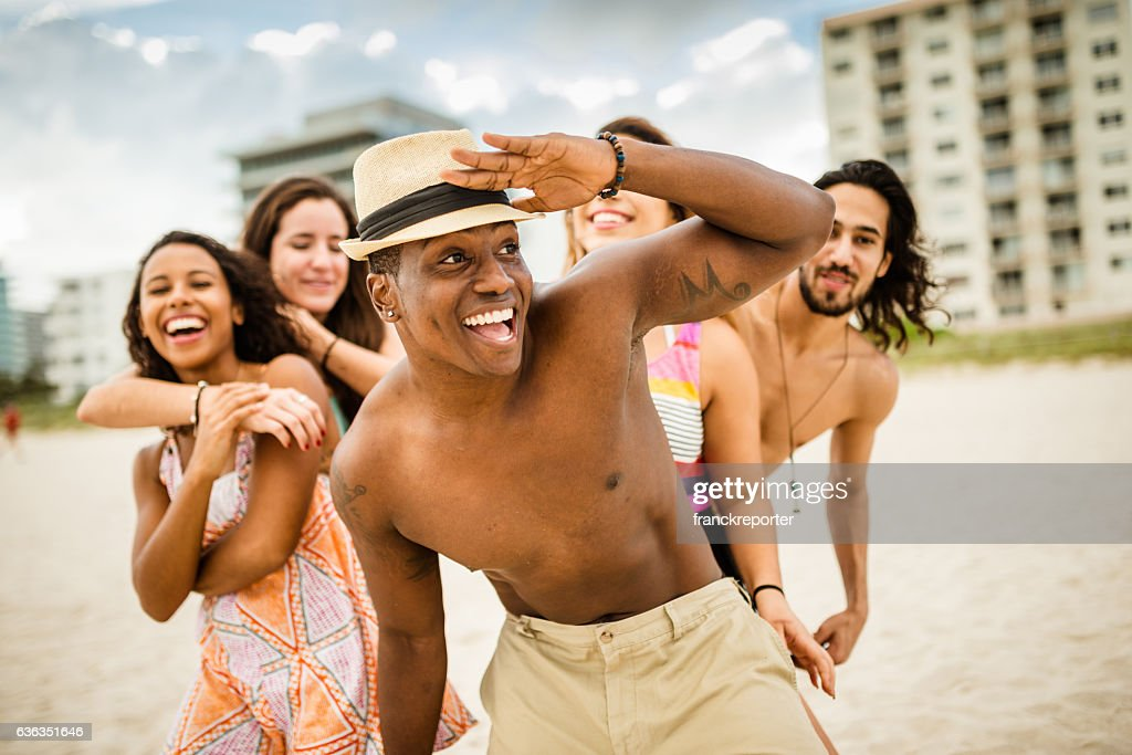 friends dancing on the beach for a party : Stock Photo