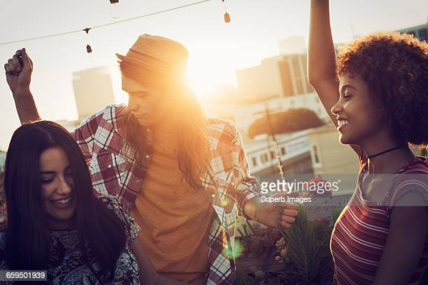 Friends dancing on urban rooftop