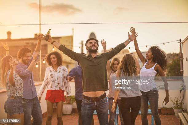 Friends dancing while enjoying party on terrace