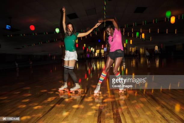 friends dancing while roller skating at illuminated roller rink - roller rink stock photos and pictures