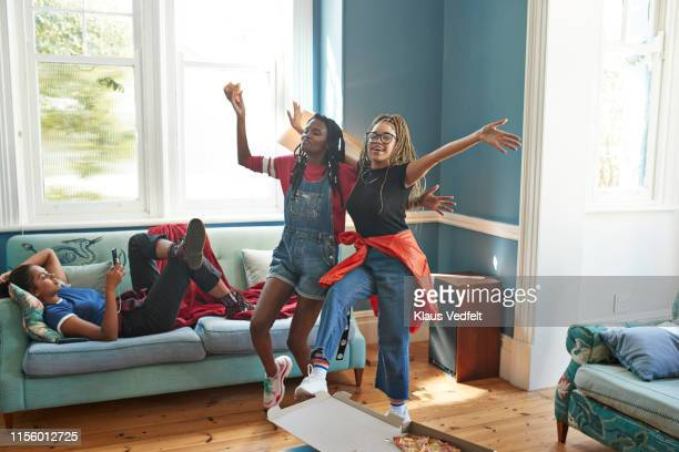 friends dancing while woman using phone - female friendship stock pictures, royalty-free photos & images