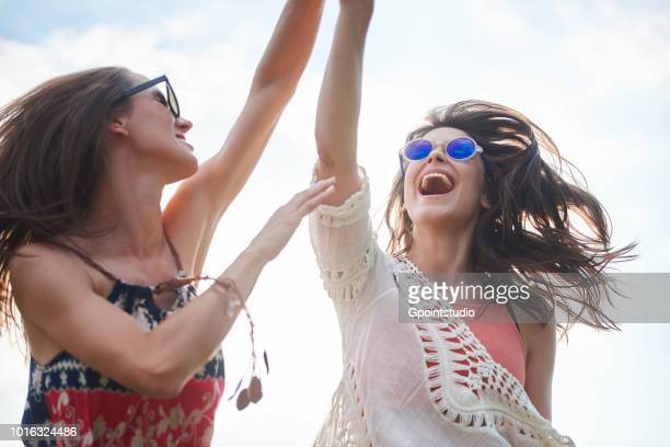 Friends dancing with arms raised in music festival