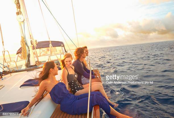 Friends dangling legs over yacht deck